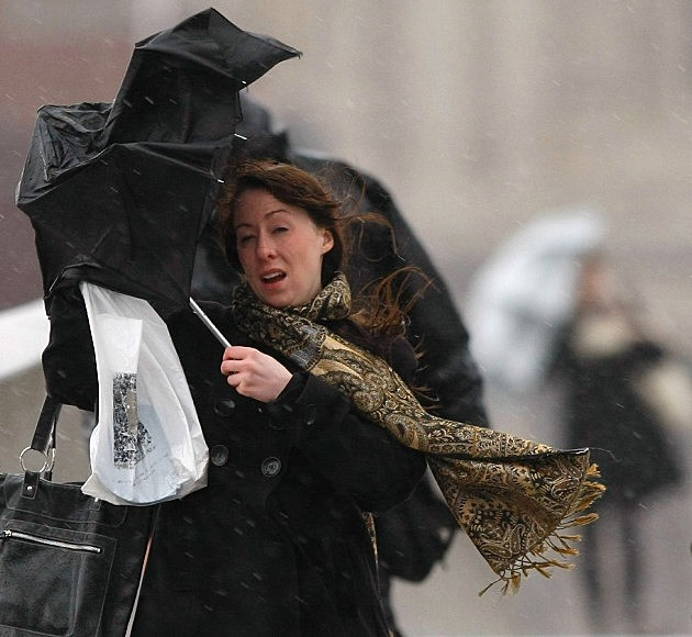 Wind blowing woman's umbrella