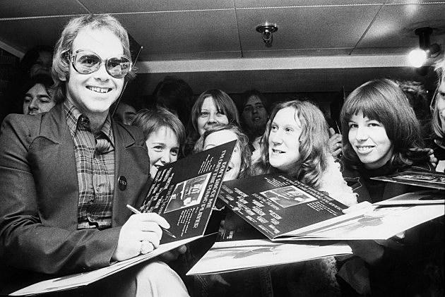 Elton John signing autographs