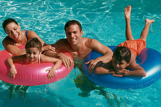 Portrait of a young couple in a swimming pool with their son and daughter
